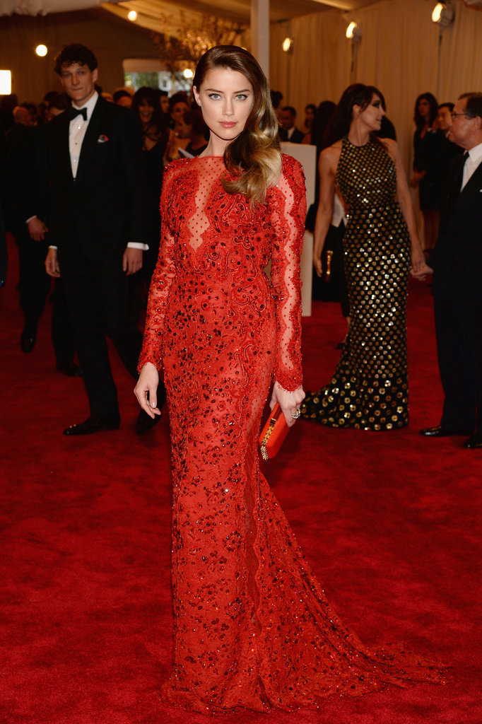 Amber Heard fit right in on the red carpet in a cherry red Emilio Pucci custom Chantilly lace gown with a matching studded minaudière, Pomellato jewels, and Casadei heels.