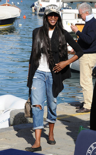 While seaside in Portofino, Naomi Campbell showed off her laid-back side in a pair of ripped boyfriend jeans. A camouflage hat, a black cardigan, studded flats, and an animal-skin bag completed her vacation style.