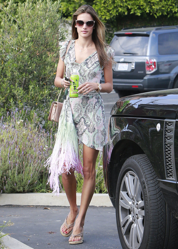 Alessandra Ambrosio embraced the warm LA weather in a printed wrap dress — note the colorful fringe detail — nude flip-flop wedges, a soft pink bag, and printed sunglasses.