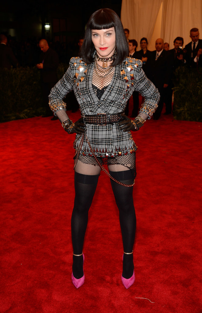 Madonna was scantily glad last night in a tartan jacket, fishnet bodysuit, thigh-high stockings which she claims she never leaves the house without.