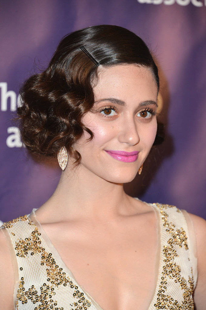 A bobby pin snuck right above a bevy of curls, just as Emmy Rossum styled her waves in March, is a modern twist on a classic Gatsby look.