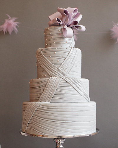 This cake combines both classic and modern elements with etched gray fondant, simple detail, and a modern bow to top it off.  Photo by Johnny Miller via Style Me Pretty