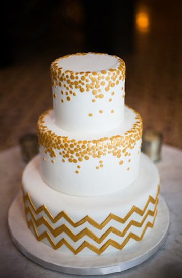 An all-white cake is given a graphic touch with a chevron base and metallic circles.  Photo by Aaron Shintaku via Green Wedding Shoes