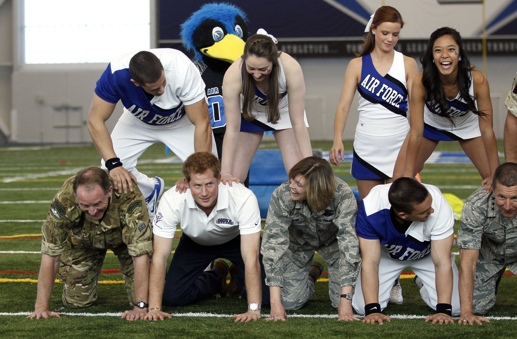 Prince Harry made a human pyramid with Air Force cheerleaders while in Colorado Springs, CO, on Sunday.