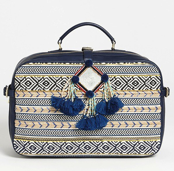 Tory Burch's Priscilla suitcase ($750) is way more structured than a typical weekender bag — but that's why it stands out from the crowd. Oh, and the intricate print and pom-poms help, too.