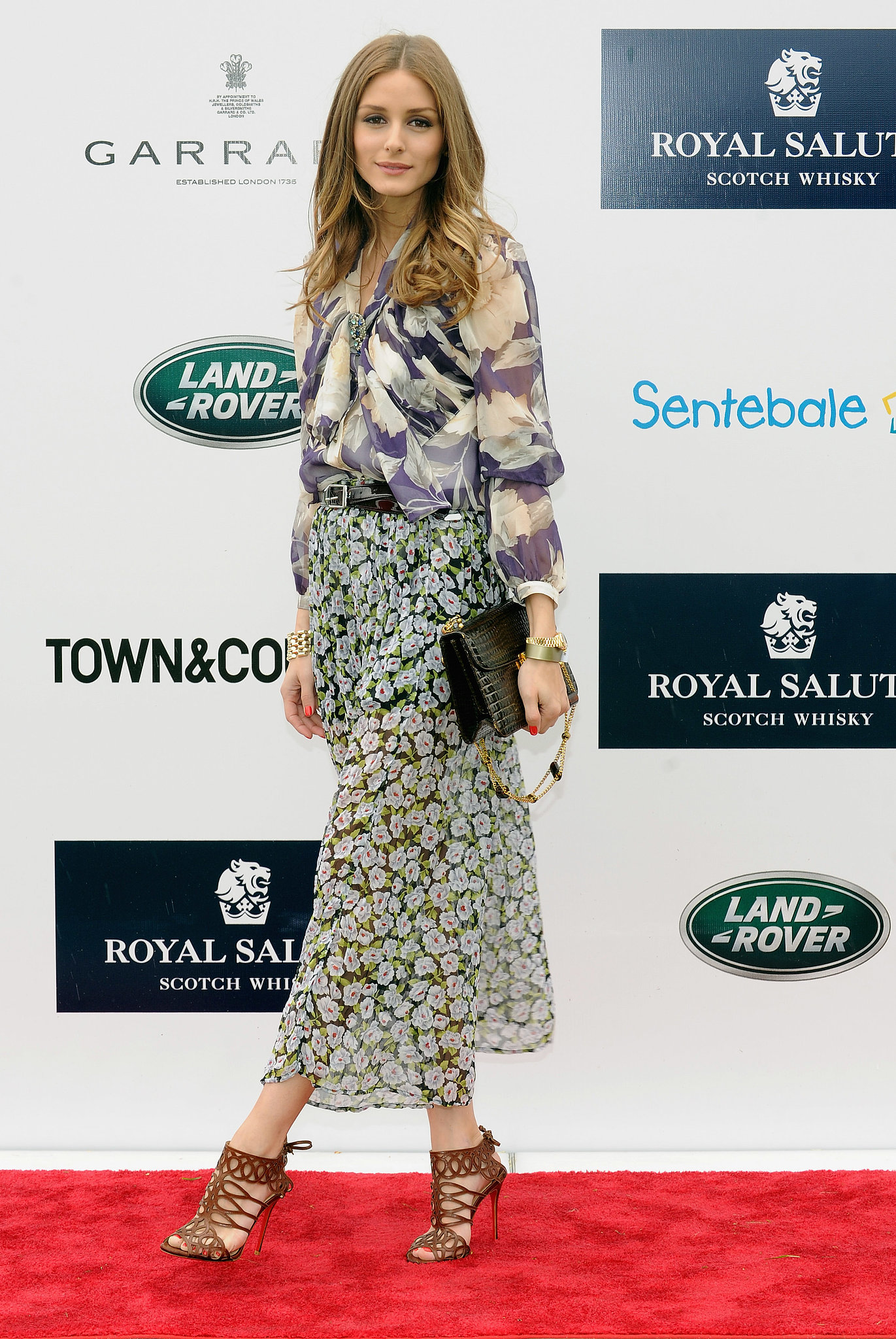 Olivia played with prints at the Sentebale Royal Salute Polo Cup in a sheer top and maxi, both adorned with watercolor floral prints. She added structure with a black belt and decadent croc bag, and finished everything off with a pair of on-trend sandal booties from Christian Louboutin.