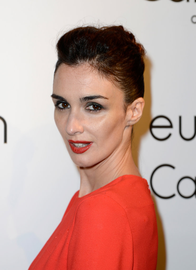Paz Vega attended the Calvin Klein party in Cannes with a red-orange lip hue that matched her bright ensemble.