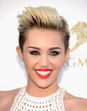 Styling her rocker hair in a slicked-back pompadour, Miley Cyrus painted her lips red and lined her eyes in black.