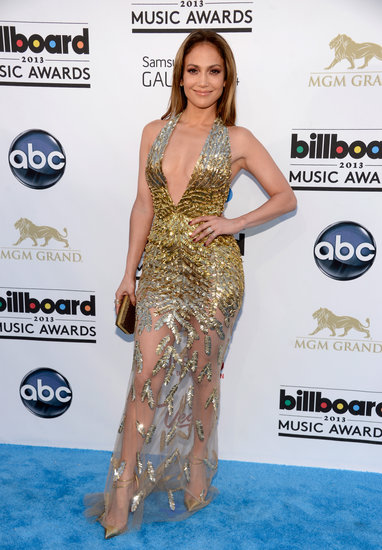 Jennifer Lopez stunned (and sparkled) in a plunging gold embellished Zuhair Murad gown with a sheer skirt and gold ankle-strap pumps.