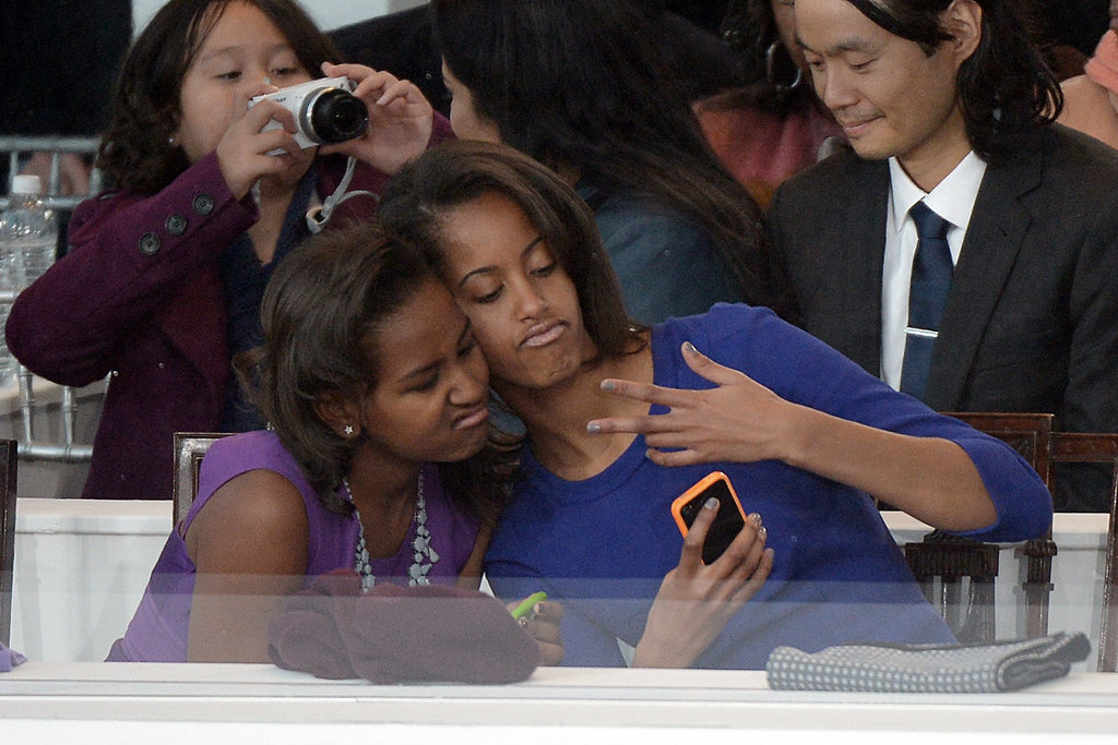 Malia and Sasha Obama got silly for a selfie while sitting in the stands during the 2013 Presidential Inauguration Parade.