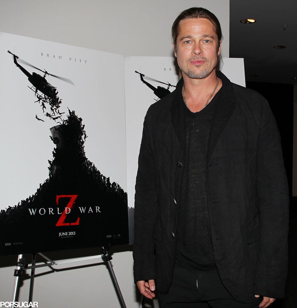 Brad Pitt stopped in front of a poster for his new flick.