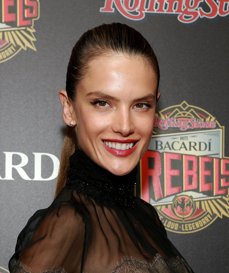 Earlier this week, Alessandra Ambrosio arrived to the Bacardi Rebels event hosted by Rolling Stone in a sheer black top with a black skirt. She opted for fun, flirty makeup with a black cat eye and red lips.