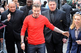 David Beckham wore a red shirt and jeans.