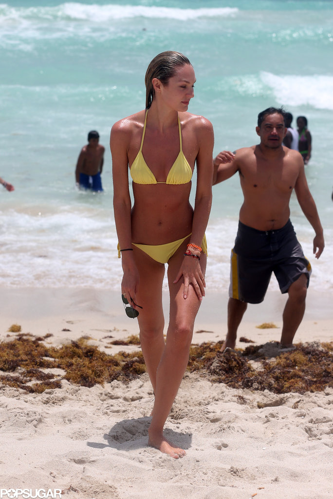 Candice Swanepoel showed off her fit figure in a yellow bikini to hit the beach in Miami.