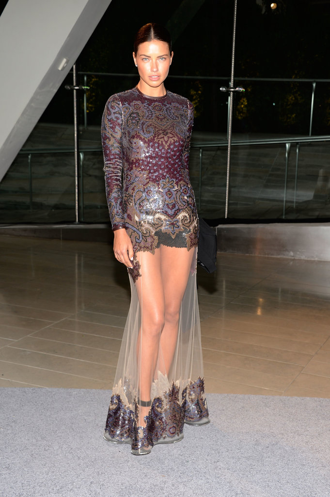 Adriana Lima put her long legs on display in a sequined gown with a sheer skirt.