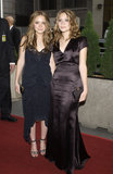 Twinning combo: Breezy beach waves tempered their moody gowns at the 2002 Emmy Awards.  Mary-Kate smiled in a ruched high-low black dress, star-embellished sandals, and a minaudière. Ashley chose a silky, chocolate-colored floor-length gown and matching clutch.