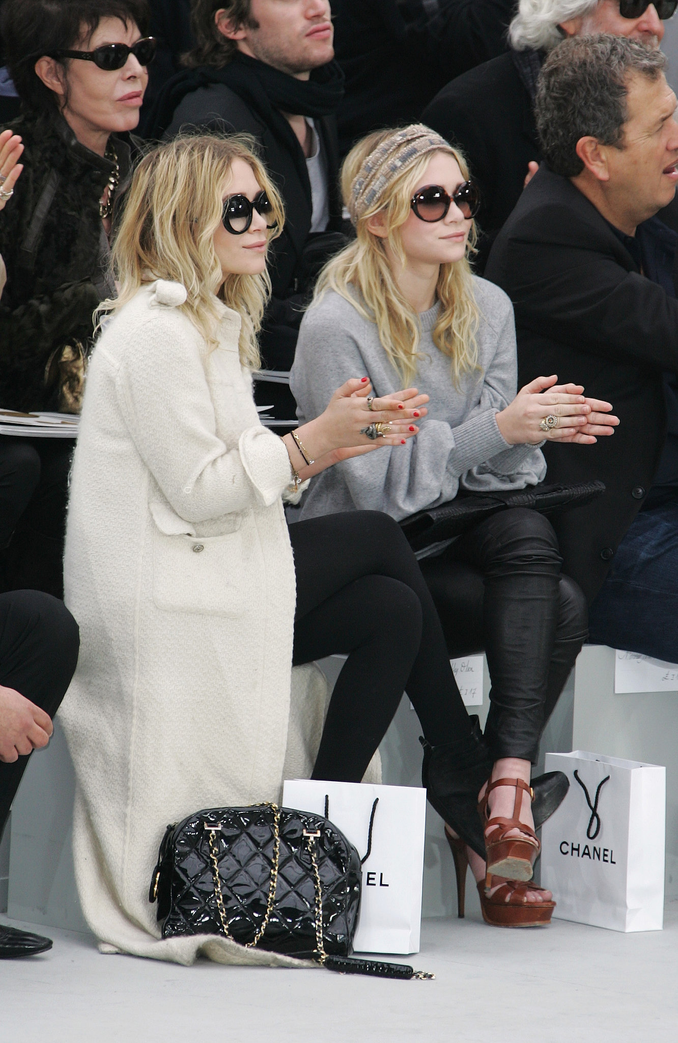Twinning combo: The girls took in the Chanel Fall/Winter 2008 show with killer eyewear.  Ashley paired a long, white tweed coat with black ankle boots, a quilted bag, and oversize shades. Mary-Kate went sporty in a gray sweater, black leather leggings, and YSL platforms and a printed headscarf.