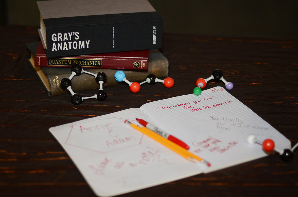 A graph paper composition book serves as a guest book on a table decorated with medical and physics textbooks.  Source: Mariana Mosli, Kismisink Photography