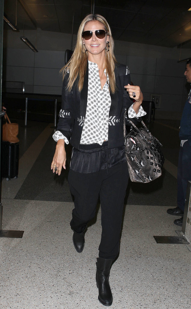Heidi Klum used a printed blouse and python bag to break up her black travel look. Note the slouchy — and hence comfy — silhouette of her pants.