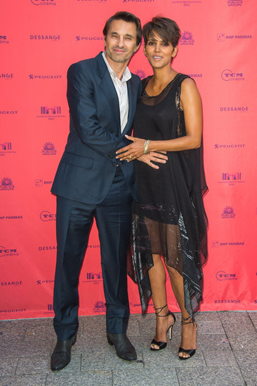 Olivier Martinez cuddled Halle Berry's baby bump on the red carpet in Paris.