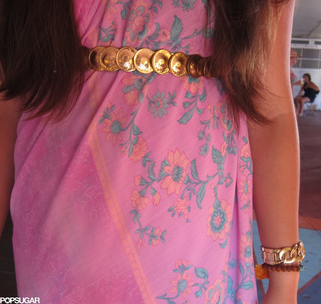 A close-up of Tamora's gold-coin belt — a gorgeous accent to her dress's softer floral-print palette.