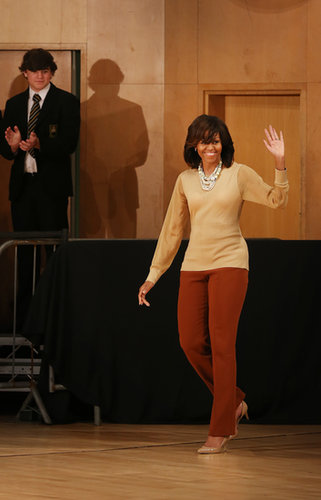 When she took off her Burberry coat, the First Lady revealed a nude sheer-sleeved blouse and rust-colored trousers at the G8 Summit in Northern Ireland.