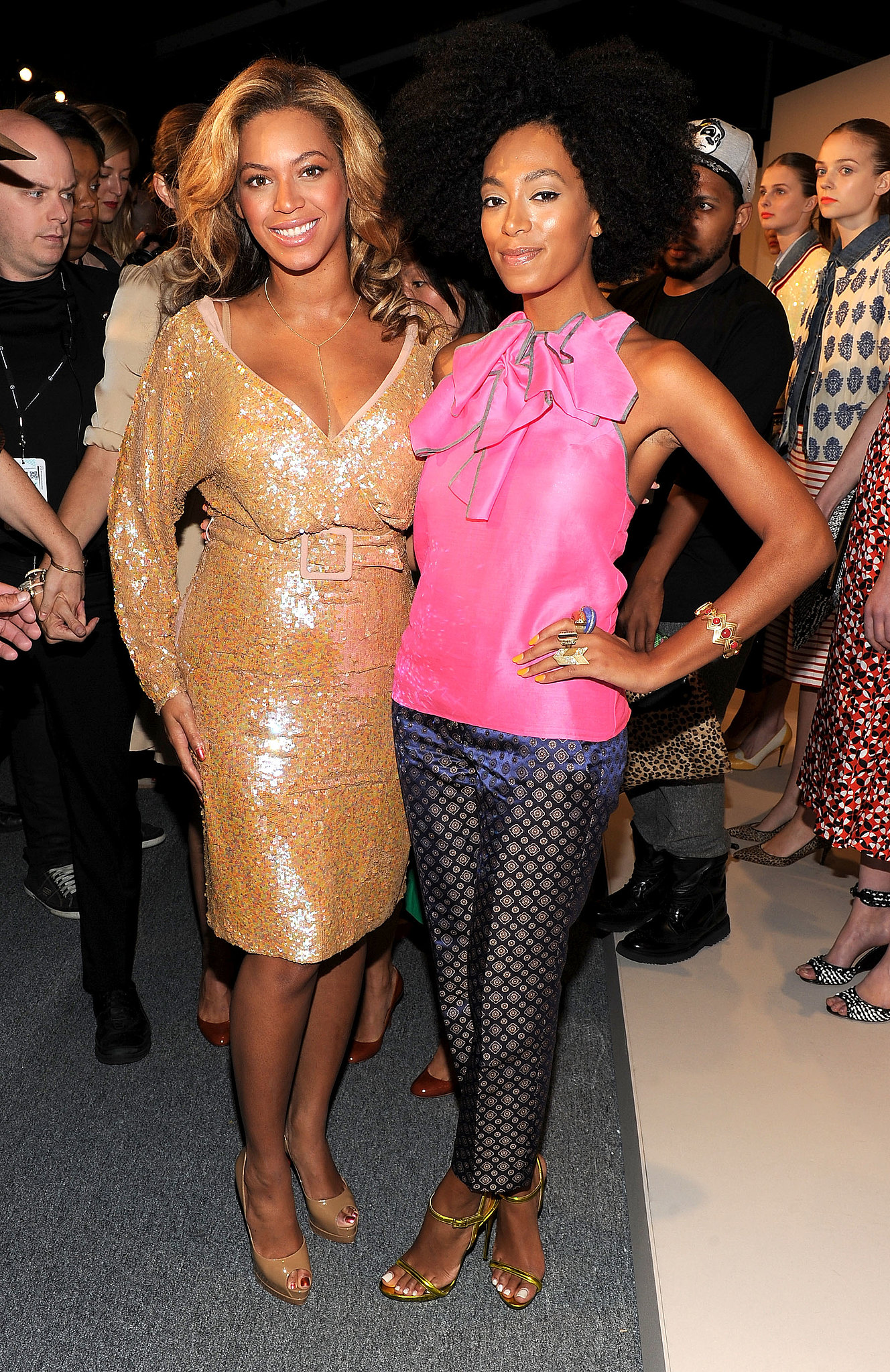 The Knowles sisters doubled up on style during NYFW Spring 2012. Solange was all smiles in a hot-pink ruffled blouse, cropped trousers, and lime-green sandals, while Beyoncé glittered in a long-sleeved, sequined number.