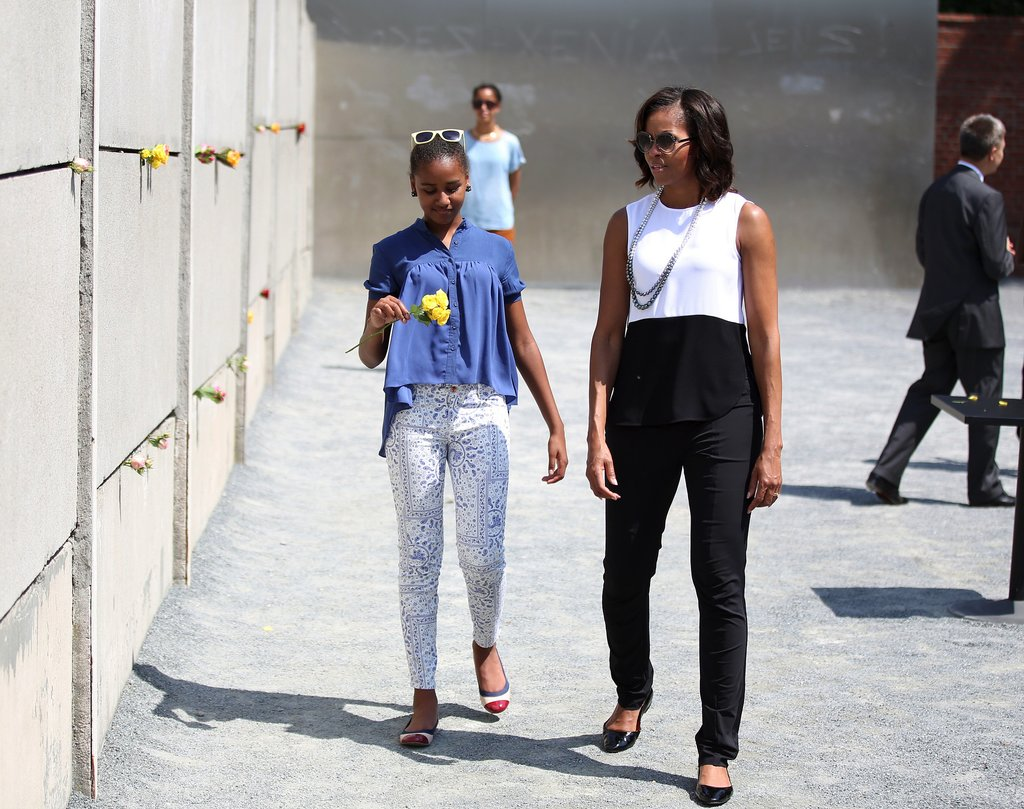 Michelle Obama toured Berlin looking chic as ever in a black and white outfit. Her gray sunglasses, matching Pearl Paradise necklace, and black patent flats were the perfect add-ons.