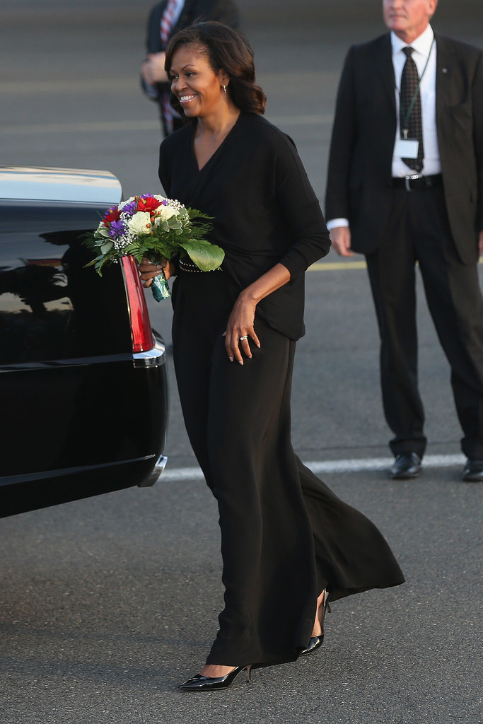 Michelle painted herself all black while in Berlin. We spy an edgy studded belt underneath her draped top.