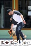 Liam Hemsworth bent down to show a furry friend some love in LA in May 2012.