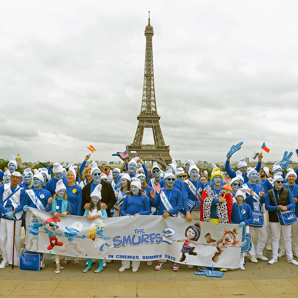 The daughter of Peyo, the late cartoonist behind The Smurfs, posed for a photo with the film's producer and a group of costumed fans in Paris, France.