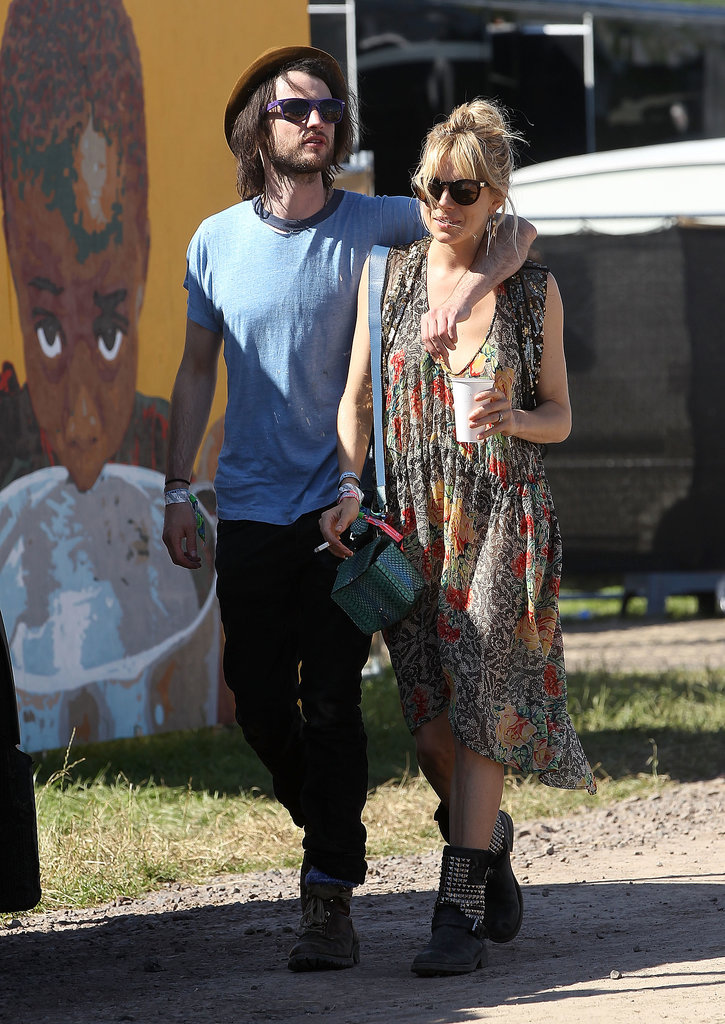 Sienna Miller cuddled with fiancé Tom Sturridge at the Glastonbury music festival in England.