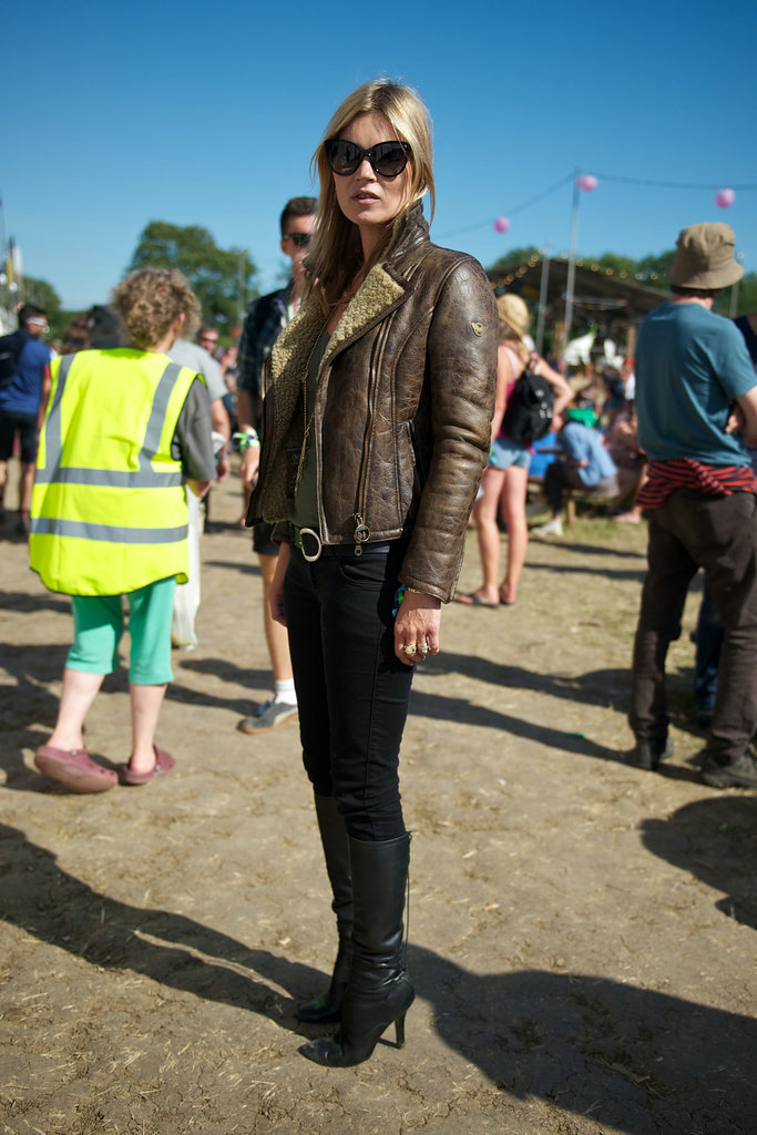 Kate Moss maintained her cool-girl status in a brown shearling leather jacket, black skinny denim, black leather boots, and dramatic cat-eye sunglasses.