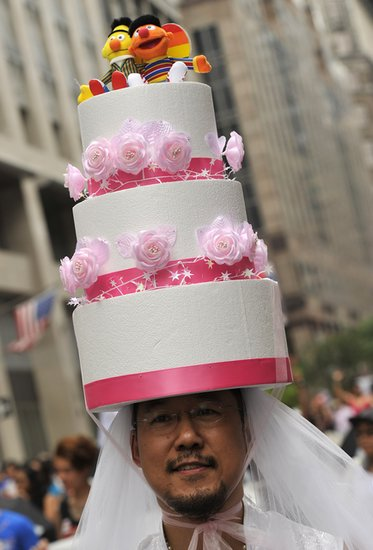 A man walked in the NYC Gay Pride Parade with a wedding cake hat.
