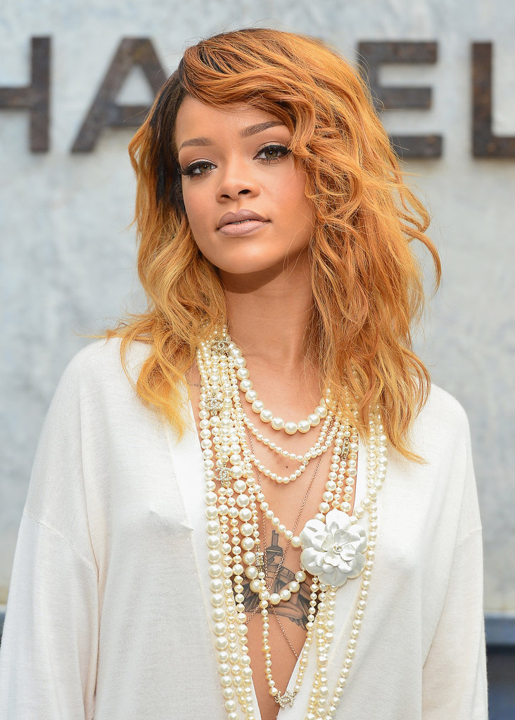 Stepping out for Chanel, Rihanna stunned in a low-cut dress that showed off her tattoo. Her beauty look focused on caramel ombré waves with dark roots. She kept her makeup natural, but her eyes were lined and defined.