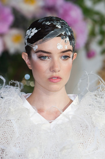 The hair at Alexis Mabille was an intricate art project with fabric flowers pasted on top of the style. The makeup was a mix of neutral shades and white accents.
