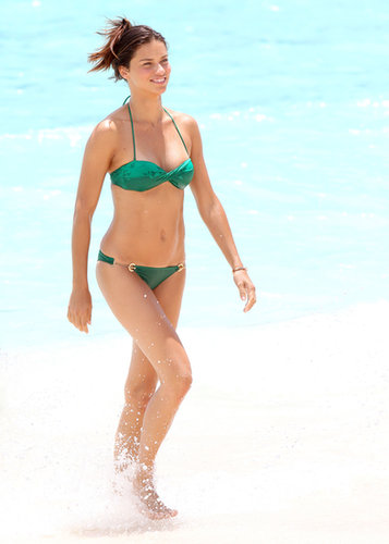 Adriana Lima splashed around in St. Barts in a bright green halter bikini — note the sexy gold chain bottoms.