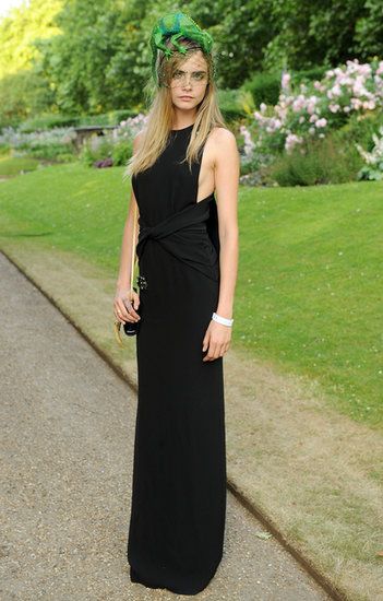 At a royal reception in London, Cara Delevingne's black gown was subtle, but her green lizard headpiece sure wasn't.