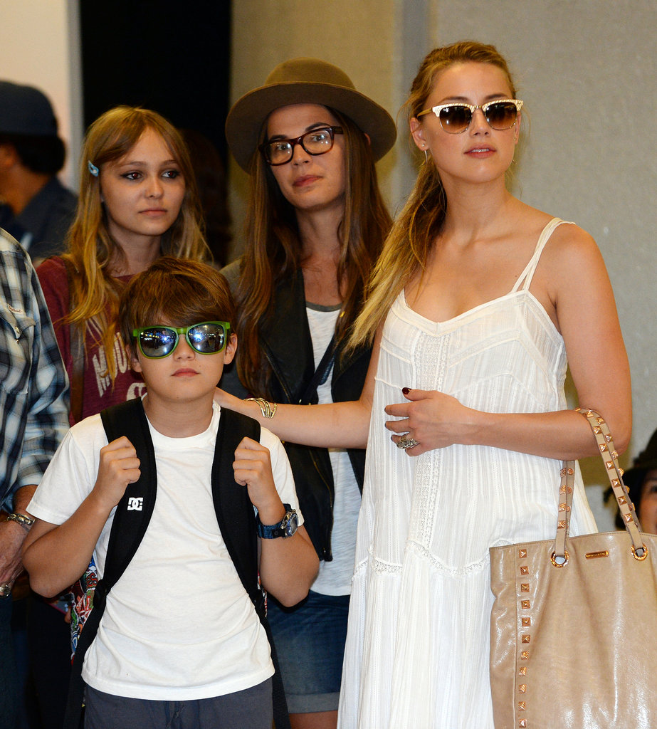 Amber Heard helped usher Johnny Depp's children through the airport in Tokyo.