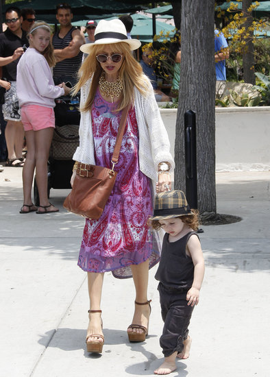 The mom ditched neutrals and got colorful in a purple printed midi dress, which she made pop even more with a white hat and a white knit cardigan.