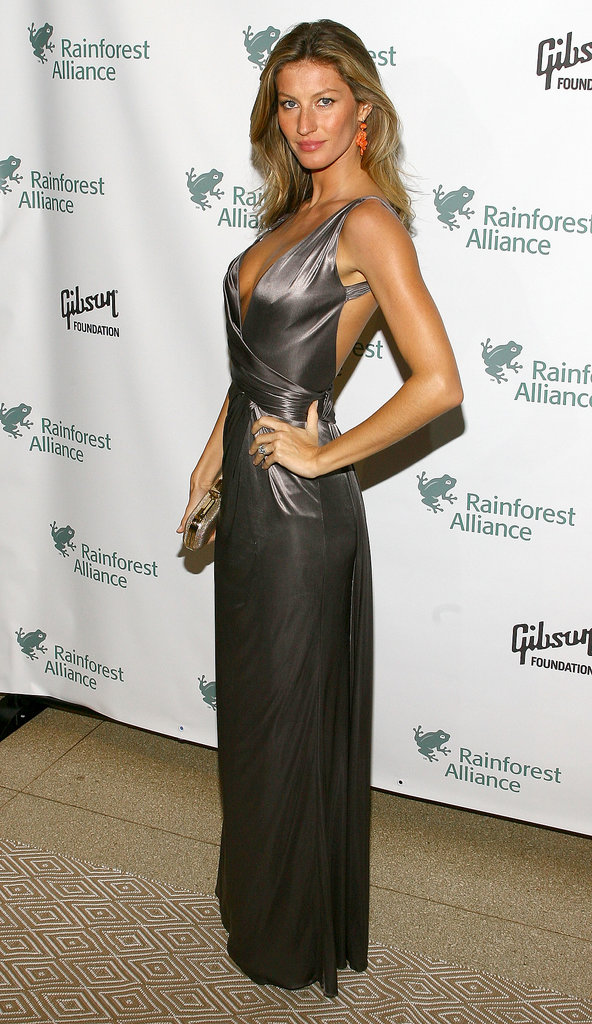 For a 2009 NYC Gala, Bündchen owned her model stance in a metallic open-back Versace wrap dress which she paired with bold coral earrings and a dazzling gold clutch.