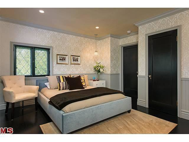 An upholstered bed frame and creamy wallpaper add a sense of luxury to this bedroom.