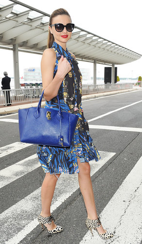 Miranda strutted her stylish stuff outside the airport in Tokyo. She mixed prints in a floral MQ Alexander McQueen dress and leopard lace-up Bionda Castana pumps, then added a bright blue bag and cat-eye sunglasses.
