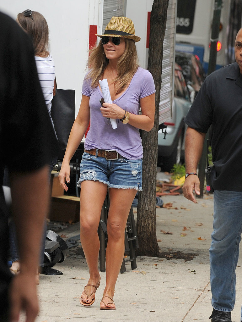 On the set of her movie, Squirrels to the Nuts, Jennifer Aniston looked casual and cool in a purple v-neck tee, distressed denim cutoffs, a straw fedora, brown belt, and nude sandals. Bring your denim cutoffs to life with a colored tee, too.