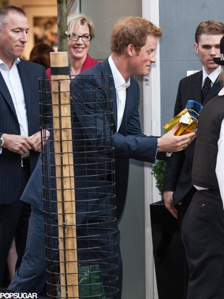 Prince Harry talked to a young woman, who handed him a gift.