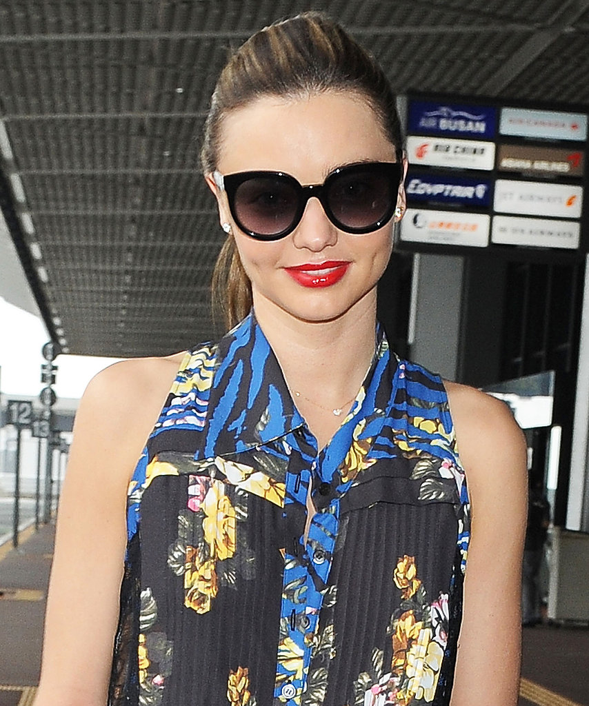 The jet-setting Miranda Kerr was spotted at the airport in Tokyo wearing a sleek ponytail, oversize black frames, and bright red lipstick.
