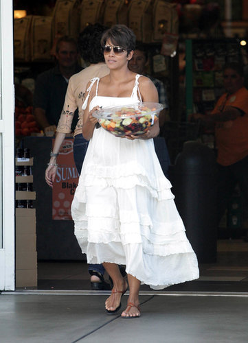 A pregnant Halle Berry beat the LA heat in a white ruffled dress and tan t-strap sandals.