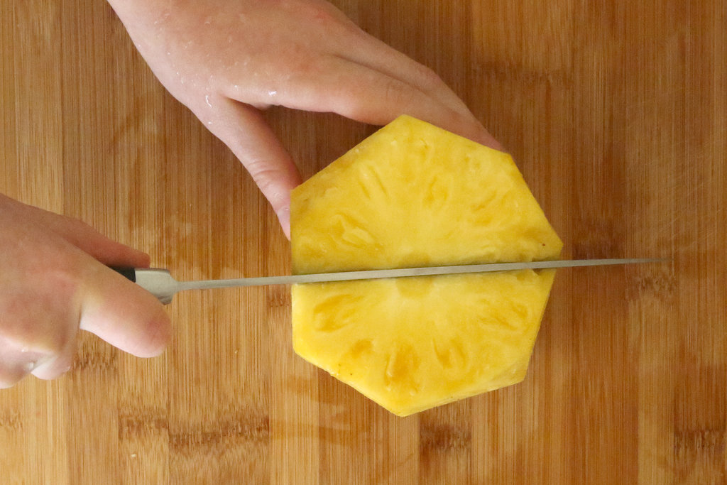 Next, cut the pineapple down the center.