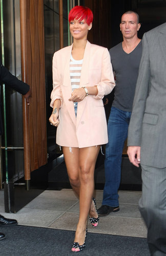Rihanna chose a pastel palette — pink Stella McCartney blazer, white sheer-stripe blouse, and light denim cutoffs — for an August 2010 NYC trip.