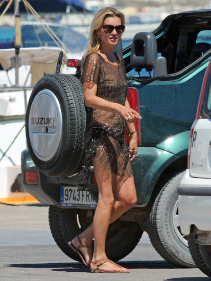 Kate perfected the beach-babe look in a netted cover-up and bikini in Spain.